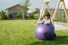 Toddler boy standing on big ball Stock Images