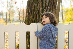 Toddler boy standing near  white fence Royalty Free Stock Image