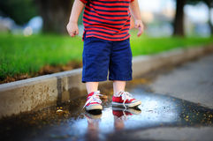 Toddler boy standing in a puddle Stock Photography