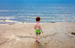 Toddler boy staring at the sea. At sunset his back to the camera Royalty Free Stock Photos