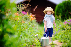 Toddler boy in straw hat watering plants in the garden Stock Photo
