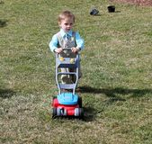 Toddler boy in a suit pushing a lawn mower  Royalty Free Stock Photography