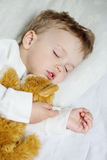 Toddler boy sweetly sleeping with a toy Royalty Free Stock Photos