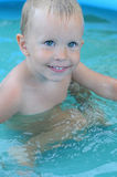 Toddler boy in swimming pool. A close up of a smiling toddler boy in a swimming pool. Child Safety stock image