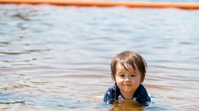 Toddler boy swimming on a summer day Stock Photo