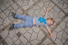 Toddler Boy tired in the temple lies on the pavement in Po Nagar Cham Tovers. Asia Travel concept.
