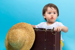 Toddler boy travel theme with a suitecase and a hat Stock Photos