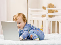 Toddler boy typing on laptop in bedroom Stock Images
