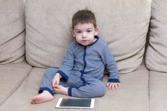 Toddler boy is using a tablet on a couch stock image