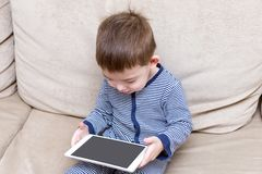 Toddler boy is using a tablet on a couch. At home royalty free stock image