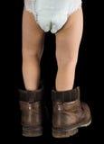Toddler Boy, Walking Away Towards Black Background In Too Big Boots Stock Photos