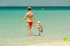 Toddler boy walking on beach with mother. Two year old toddler boy walking on beach with mother Stock Photo