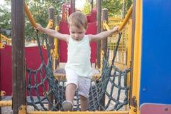 Toddler boy walking on blue net bridge stock images
