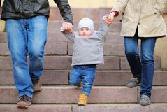 Toddler boy walking with his parents Royalty Free Stock Images