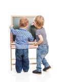 Toddler boys drawing on chalkboard over white Stock Photo