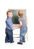Toddler boys drawing on chalkboard over white Royalty Free Stock Images