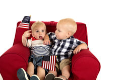 Toddler boys sitting in a red chair holding American flags Stock Images