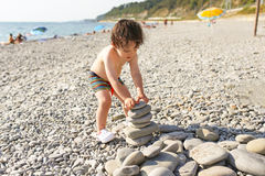 Toddler building pebbles tower on the beach Royalty Free Stock Photography