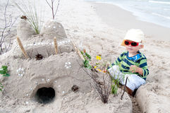 Toddler Building Sand Castle. Little boy at the beach in front of a sand castle Royalty Free Stock Photo