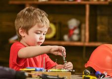 Toddler on busy face plays with bolts at home in workshop. Kid boy play as handyman. Child cute and adorable playing Stock Photography