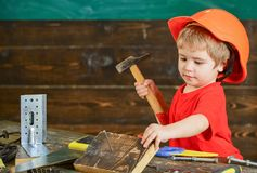 Toddler on busy face plays with hammer tool at home in workshop. Child in helmet cute playing as builder or repairer. Repairing or handcrafting. Kid boy play stock photo