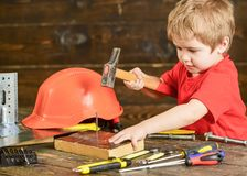 Toddler on busy face plays with hammer tool at home in workshop. Handcrafting concept. Kid boy play as handyman. Child Stock Image