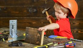 Toddler on busy face plays with hammer tool at home in workshop. Kid boy play as handyman. Handcrafting concept. Child Royalty Free Stock Images