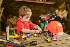 Toddler on busy face plays with tools at home in workshop. Kid boy play as handyman. Child cute and adorable playing Royalty Free Stock Photos