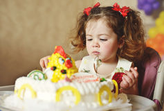 Toddler with cake. Cute toddler girl with her birthday cake royalty free stock photo