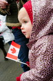 Toddler with Canadian flag. Looking out in the crowd, a toddler holds a Canadian flag royalty free stock images