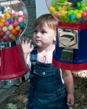 Toddler between candy bins. Toddler (girl) between candy bins, looking directly at candy with desire royalty free stock photos