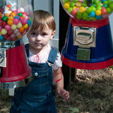 Toddler between candy bins. Cute young girl between candy bins, looking directly at candy with desire royalty free stock photography