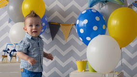 A toddler carefully touches colorful balloons. A boy afraid of touching balloons ties together in front of him stock footage
