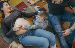 Toddler caressing belly of his pregnant mother stock photo