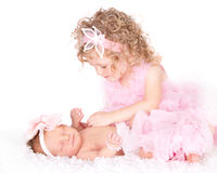 Toddler caring for her infant sister Stock Photography