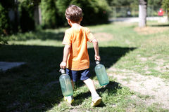 Toddler carrying his milk from farm Stock Images