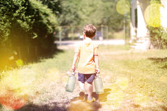 Toddler carrying his milk from farm Stock Image