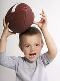 Toddler Catching Football. Cute toddler boy catching football with happy expression stock photo
