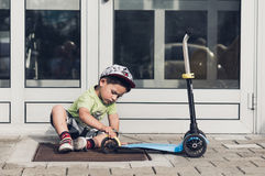 Toddler checking a scooter Royalty Free Stock Photography
