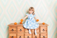 Toddler child baby girl in light blue dress seriously sitting on the wooden chest of drawers and holding fresh orange stock images