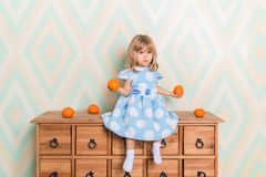 Toddler child baby girl in light blue dress seriously sitting on the wooden chest of drawers and holding fresh orange stock photography