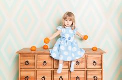 Toddler child baby girl in light blue dress seriously sitting on the wooden chest of drawers and holding fresh orange royalty free stock photography