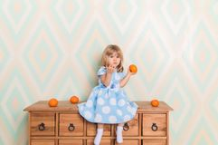 Toddler child baby girl in light blue dress sitting on the wooden chest of drawers seriously looking furrowing brows and royalty free stock images