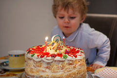 Toddler child blowing candles on his 2 birthday cake Royalty Free Stock Photo