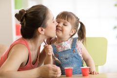 Cute child girl is having healthy breakfast. Her mother is kissing her with love. Child is sitting at table and eats yoghurt stock photography