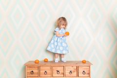 Toddler child girl in light blue dress standing on wooden chest of drawers and holding fresh orange mandarin in hand and royalty free stock photos