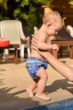 Toddler child goes to the hands of his father to the pool royalty free stock photo