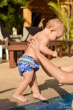 Toddler child goes to the hands of his father to the pool Stock Image