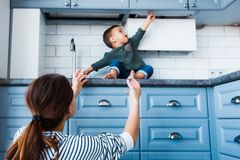 Toddler child in kitchen, children safety at home concept. Mom protects the child from dangers in the kitchen Royalty Free Stock Photography