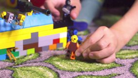 Toddler child little boy with blondi hair sitting surrounded by toys and playing with building blocks lego human figure stock video